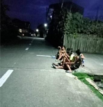 Several children sitting beside the street
