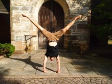 Alex does handstands in front of the church door