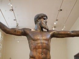 the bronze statue of Zeus or Poseidon, found in the sea off of Evia, which depicts one of the gods (no one really knows which one) with his arms outstretched and holding a thunderbolt or trident in his right hand