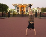Alex does a handstand at Al Alam Palace in Muscat