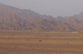 three Omani ladies in abayas walk across a wide expanse