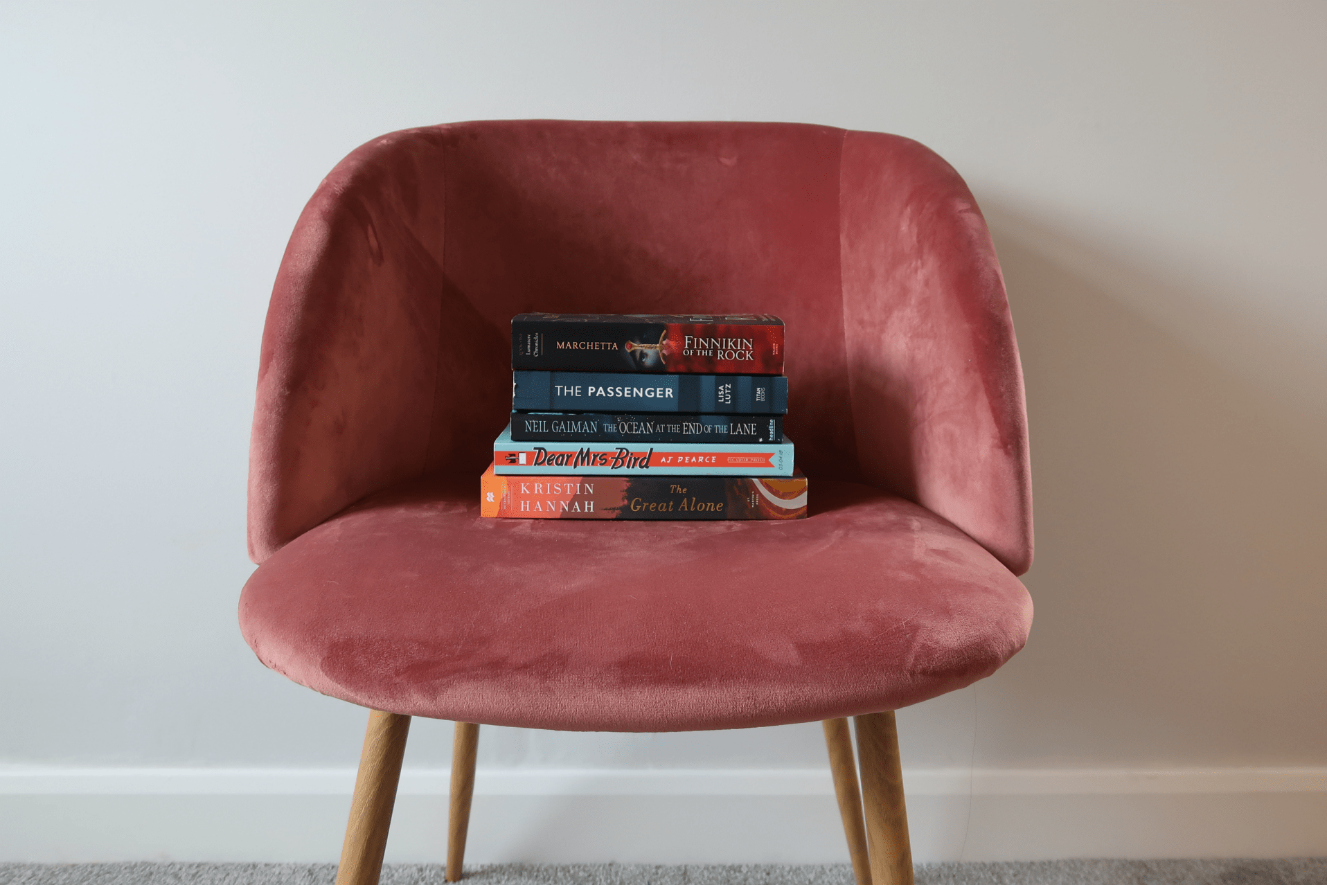 stacked books on velvet chair