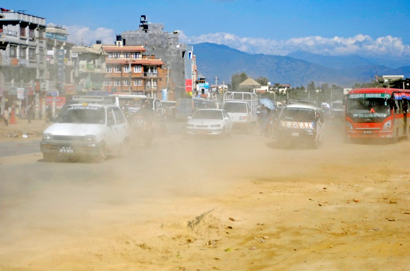 Vehicles passing through a badly damaged road section of Ring Road, at Satdobato, Lalitpur. Action plan against air pollution to begin soon.