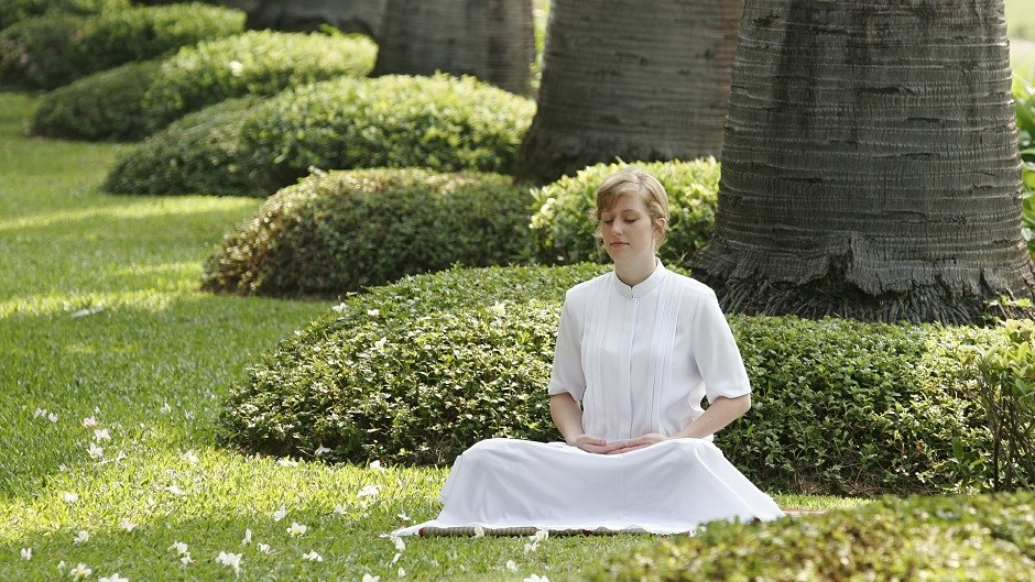 a lady meditating in a serene environment