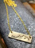 "Isaiah 8:17 hand stamped with mountain scene on horizontal gold tone rectangle includes 18"" gold tone chain. $28"