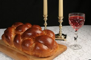 A table set for Shabbat with challah bread candlesticks and wine Black background complete view