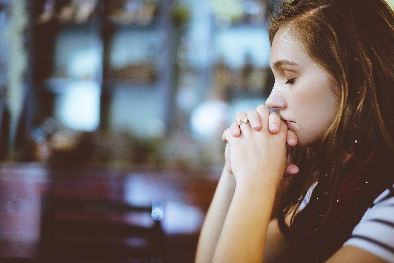 Girl praying alone in a Church