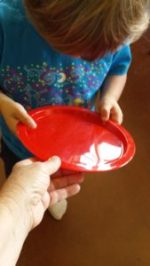 Teacher handing Transition Object (plate) to student