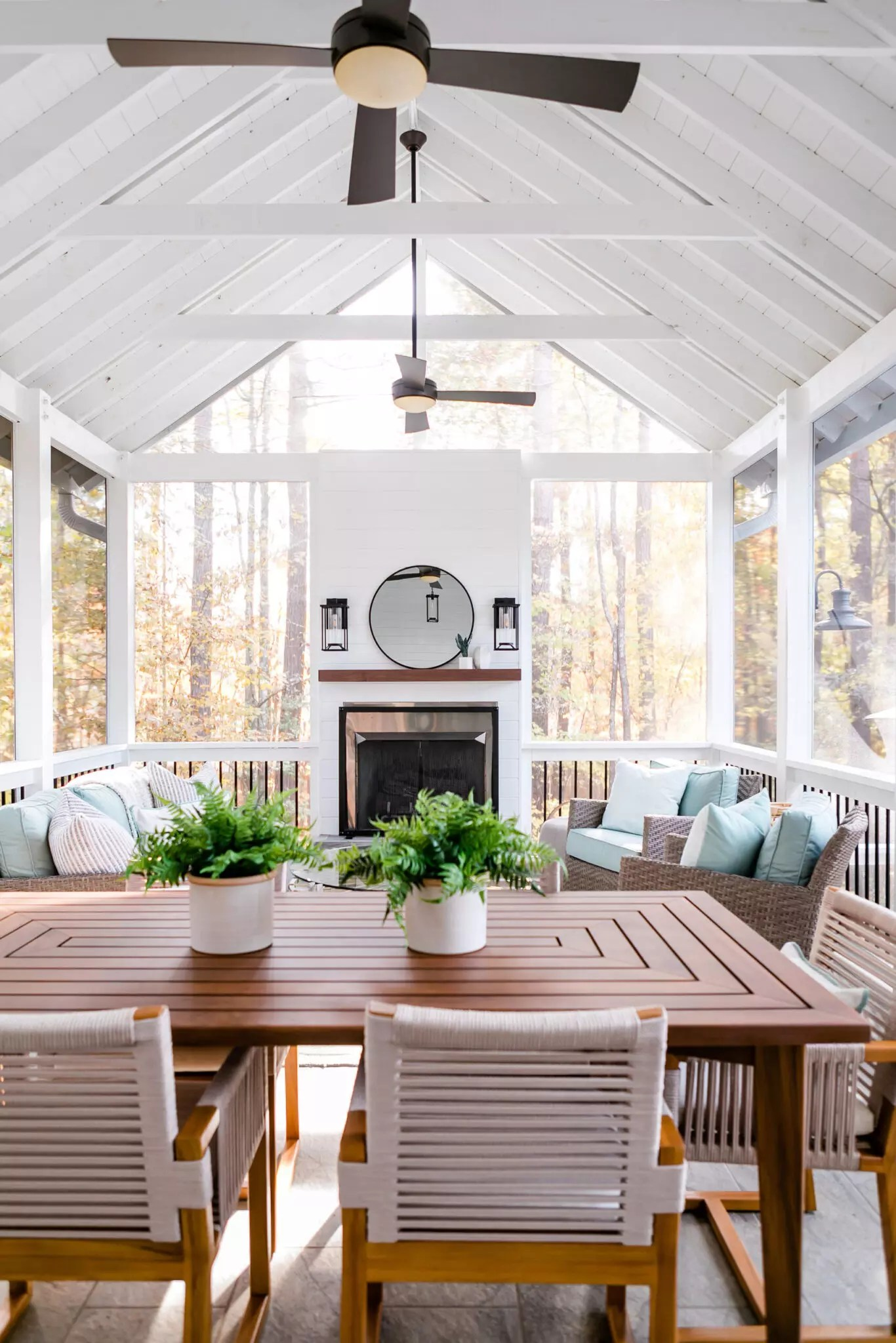 Stunning view of the screen porch layout with teak dining set and amazing outdoor furnishings - Catherine French Design