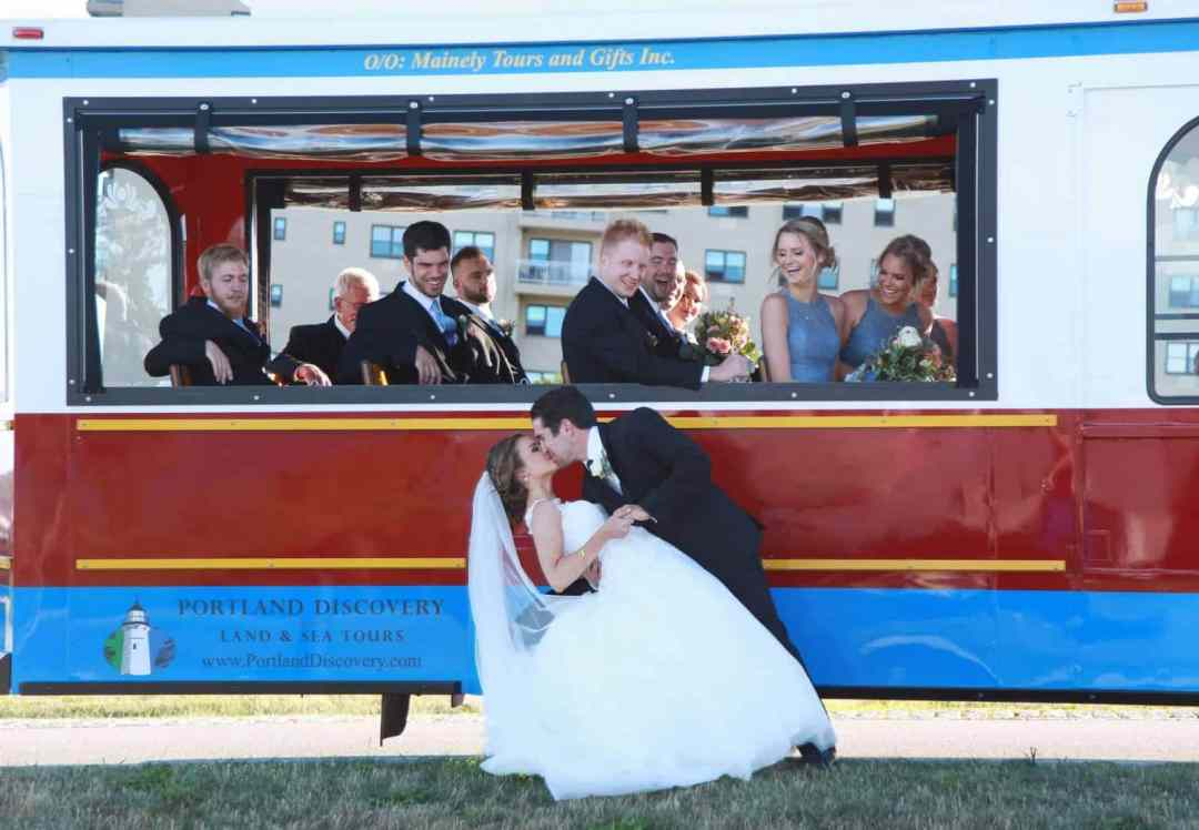 bride and groom kissing in front of trolley, bridal party watching from the inside