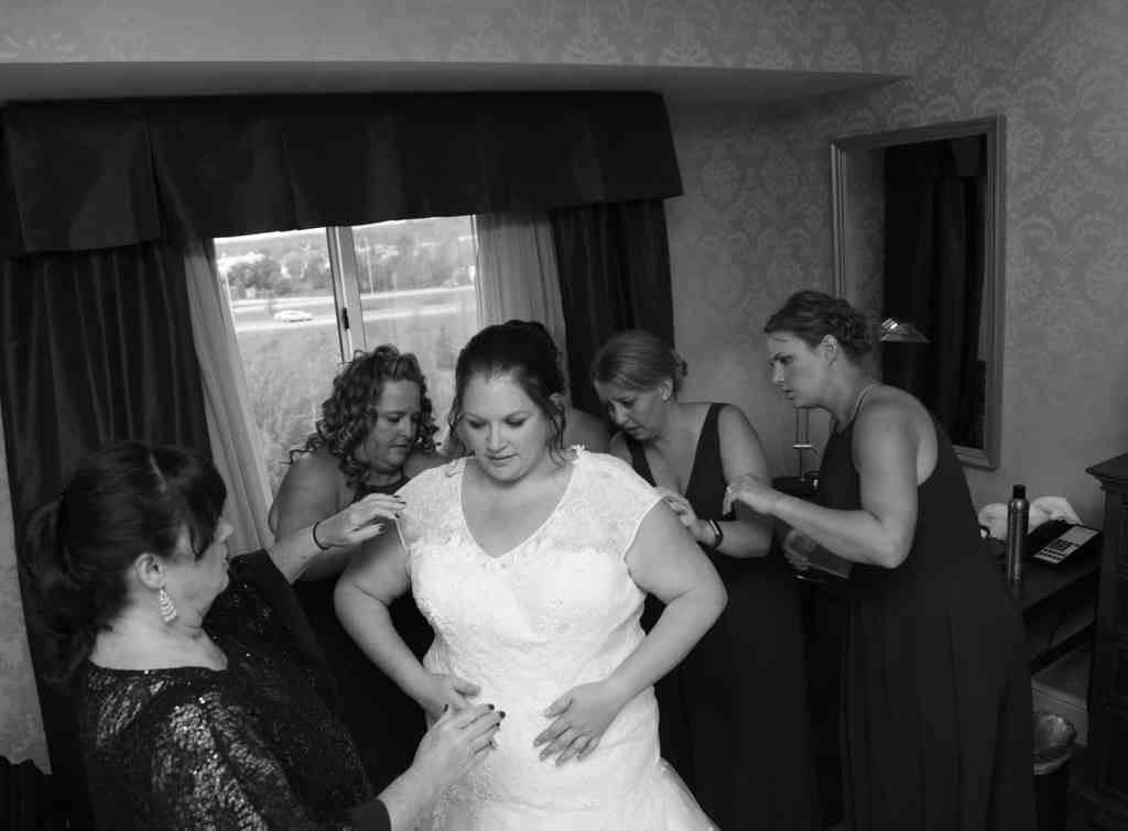 Bridesmaids helping the bride into her dress photo in black and white.