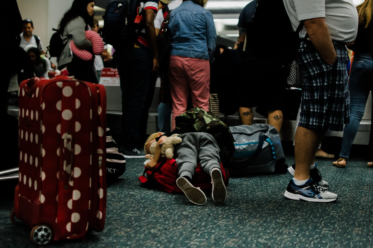 little boy laying on luggage in san diego airport {san diego lifestyle newborn baby child family photographer}