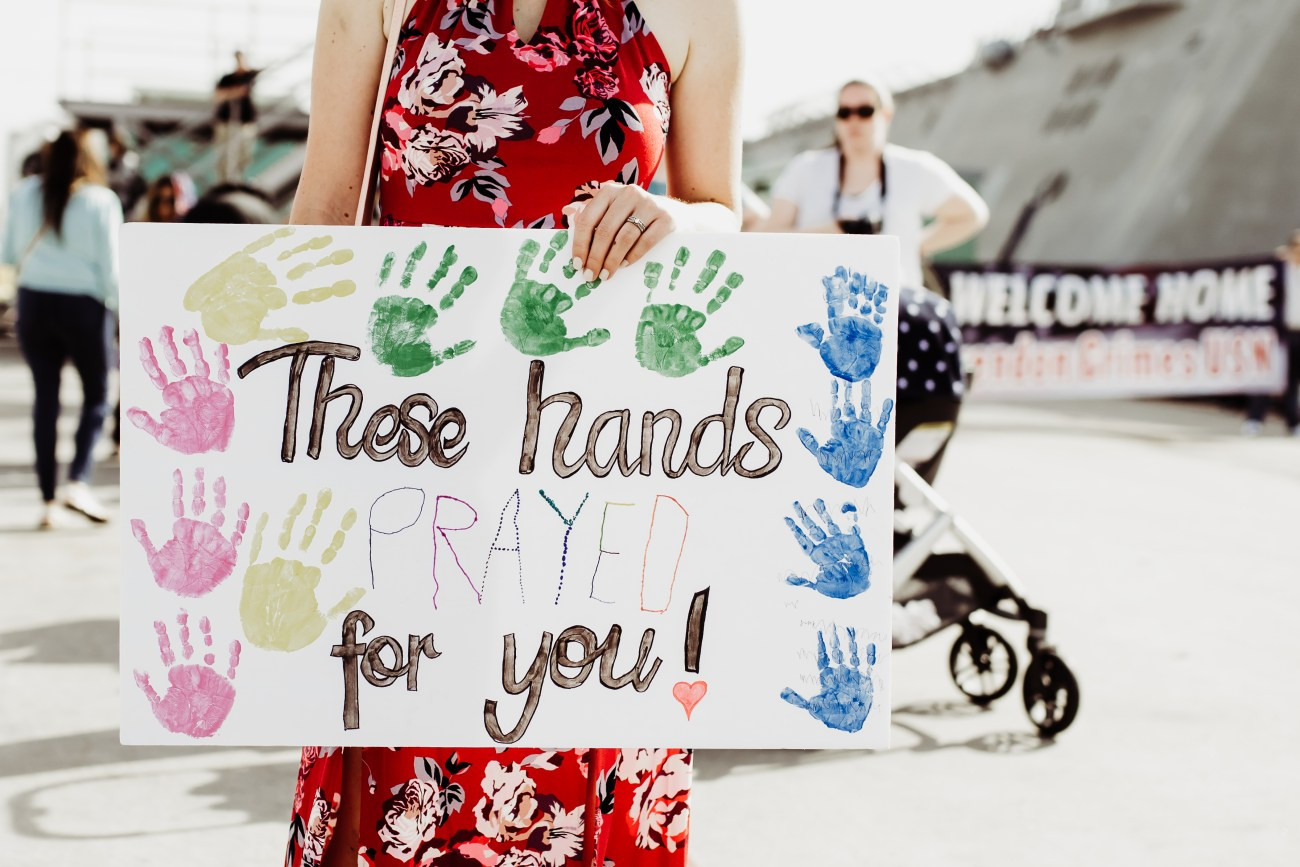 mother holding praying sign at san diego navy military homecoming {virginia beach lifestyle newborn child couples family maternity engagement photographer}