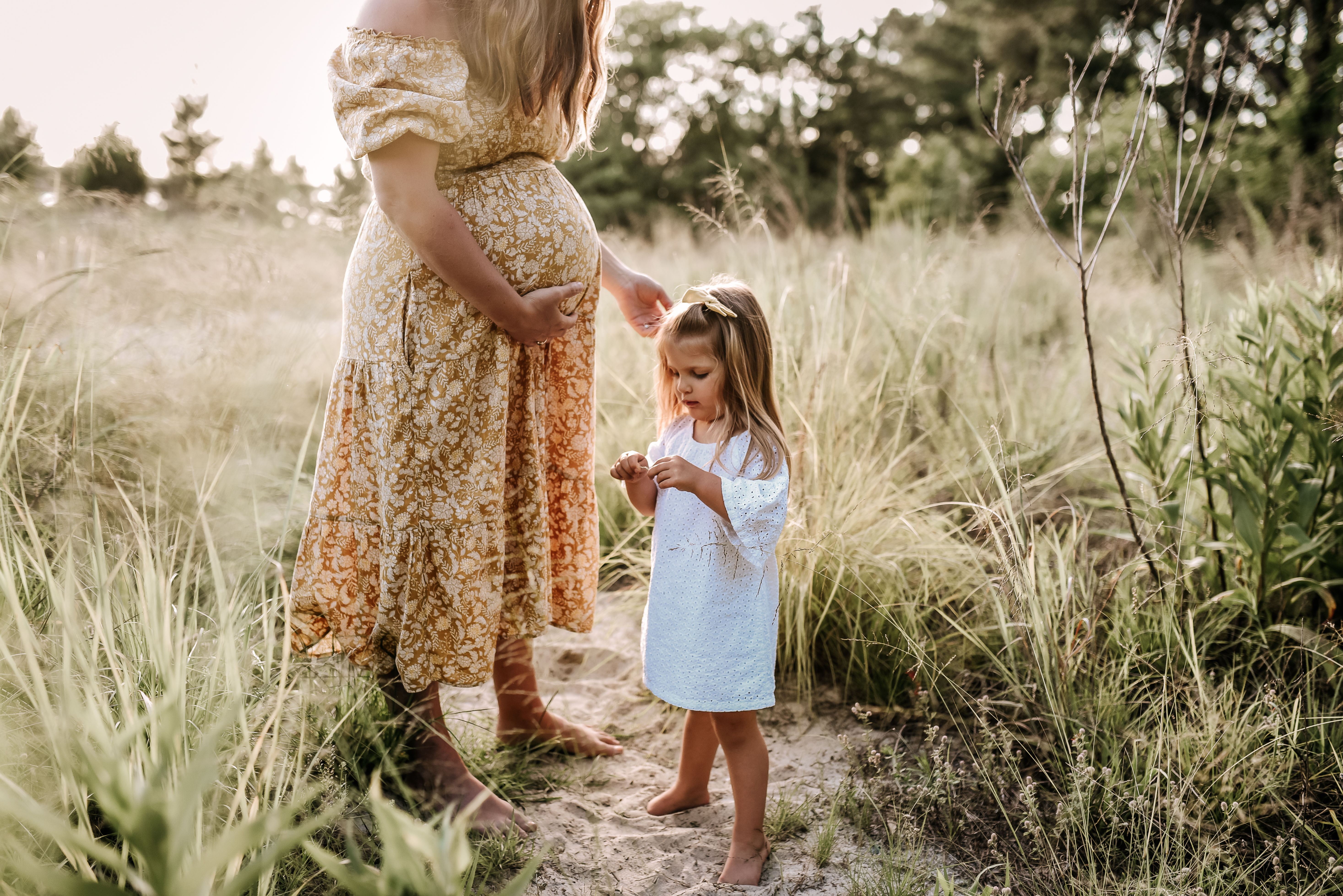 pregnant mama plays in grass beach field with baby girl holding flower the Narrows {virginia beach chesapeake lifestyle child couples family military homecoming photographer holistic healer transformational mentor}