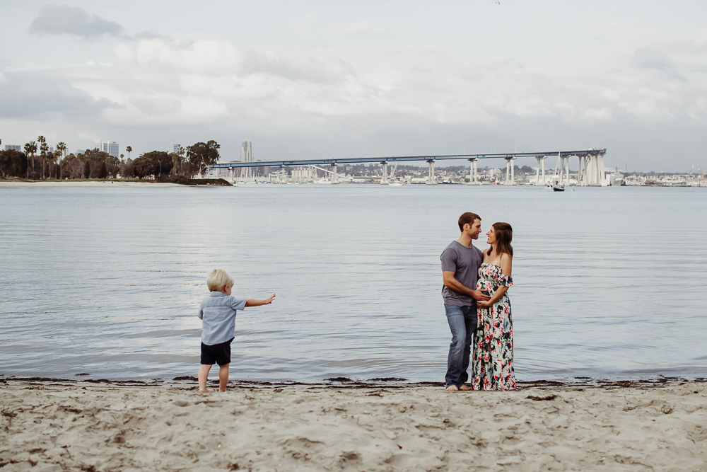 pregnant mother and father laughing holding baby boy coronado island maternity photography {san diego lifestyle newborn child couples family maternity engagement photographer}