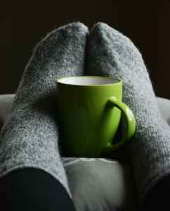 Feet in cozy socks wrapped around mug