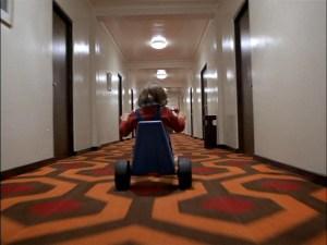 Child riding big wheel in hallway in the shining