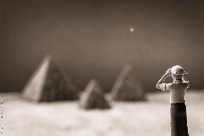 Une figurine de Tintin en avant plan qui semble regardée vers des pyramides au loin.