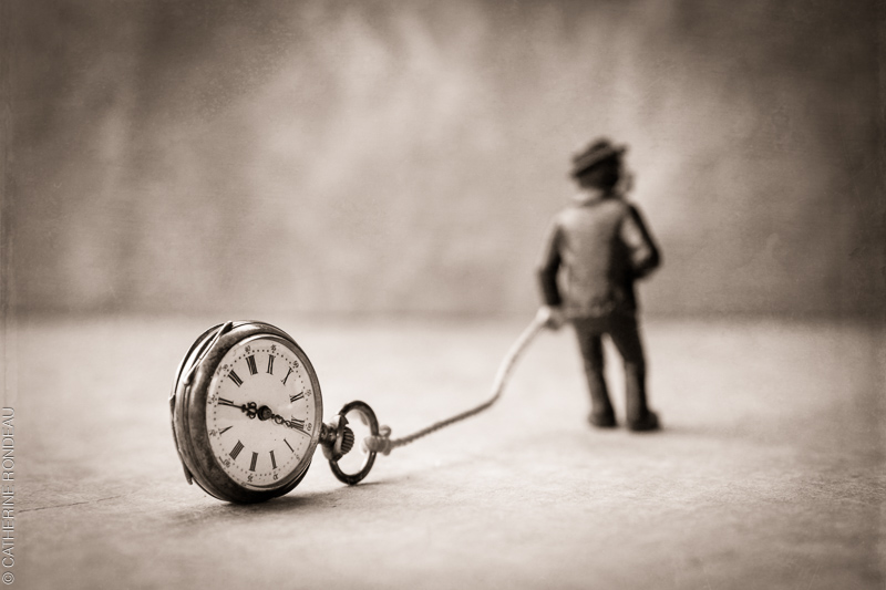 Figurine of a man pulling an old watch.