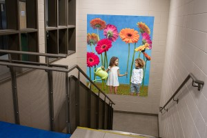 Picture of 2 children with giant flowers suspended in a staircase