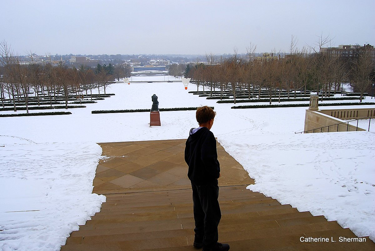 "Our young guest from Sydney, Australia, contemplates the snowy view.   Beyond, Auguste Rodin's ""The Thinker"" ponders the giant shuttlecocks that seemed to have landed on the snow in front of the Nelson Atkins Museum of Art."