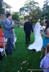 Every guest seems to have a camera to capture the bride and groom as they walk down the rose-strewn aisle in this Napa Valley, California, wedding.