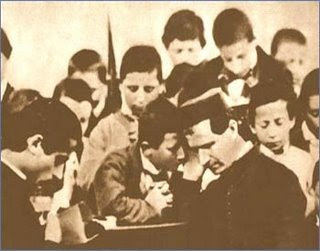 St. John Bosco hearing confessions of his boys.