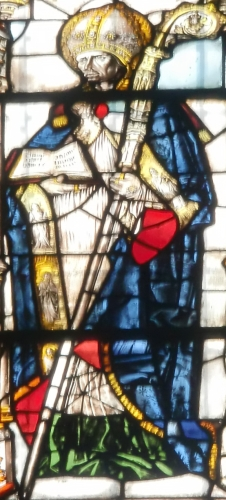 detail of a stained glass window of Saint Jucudus of Aosta in episcopal dress, holding a silver crozier and an open missal; 1493 by Pietro Vaser; Cathredral of Santa Maria Assunta, Aostal, Italy; photographed in February 2010 by Laurom; swiped from Wikimedia Commons
