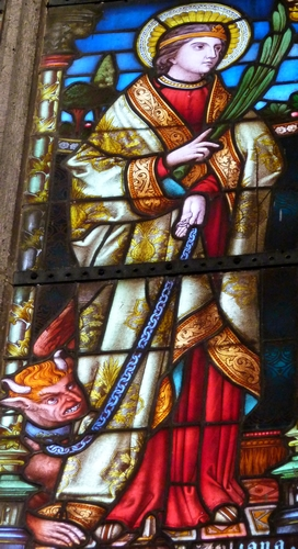 detail of a stained glass window of Saint Juliana of Nicomedia; created in 1889 by Glasmalerei Schneiders und Schmolz based on designs by Heinrich Wiethase; northern choir window of the Catholic Church of Saint Mary Magdalene and Saint Andrew, Knechtsteden, Dormagan, Rhein-Kreis Neuss, North Rhine-Westphalia, Germany; photographed on 12 November 2012 by GFreihalter; swiped from Wikimedia Commons; click from source image