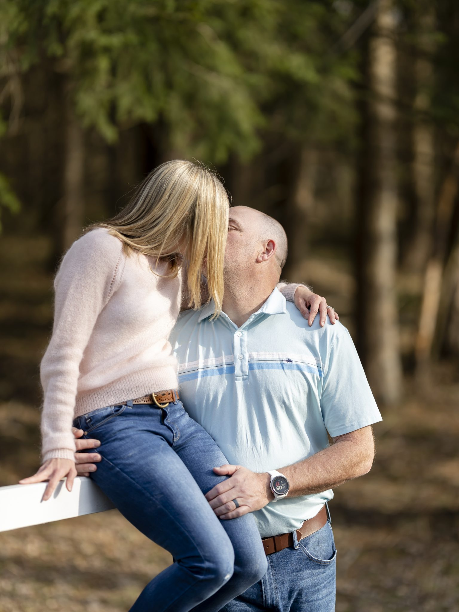 Husband and wife in pink sweater, blue polo and jeans, natural lighting, natural setting, woods, Professional portraits, couples portraiture, Keuka Lake, Fingerlakes Region, Vacation photos, Fingerlakes vacation, Penn Yan, New York, family photoshoot, family pictures, Husband and wife pictures holding hands, sitting on a fence, kissing, happiness, love