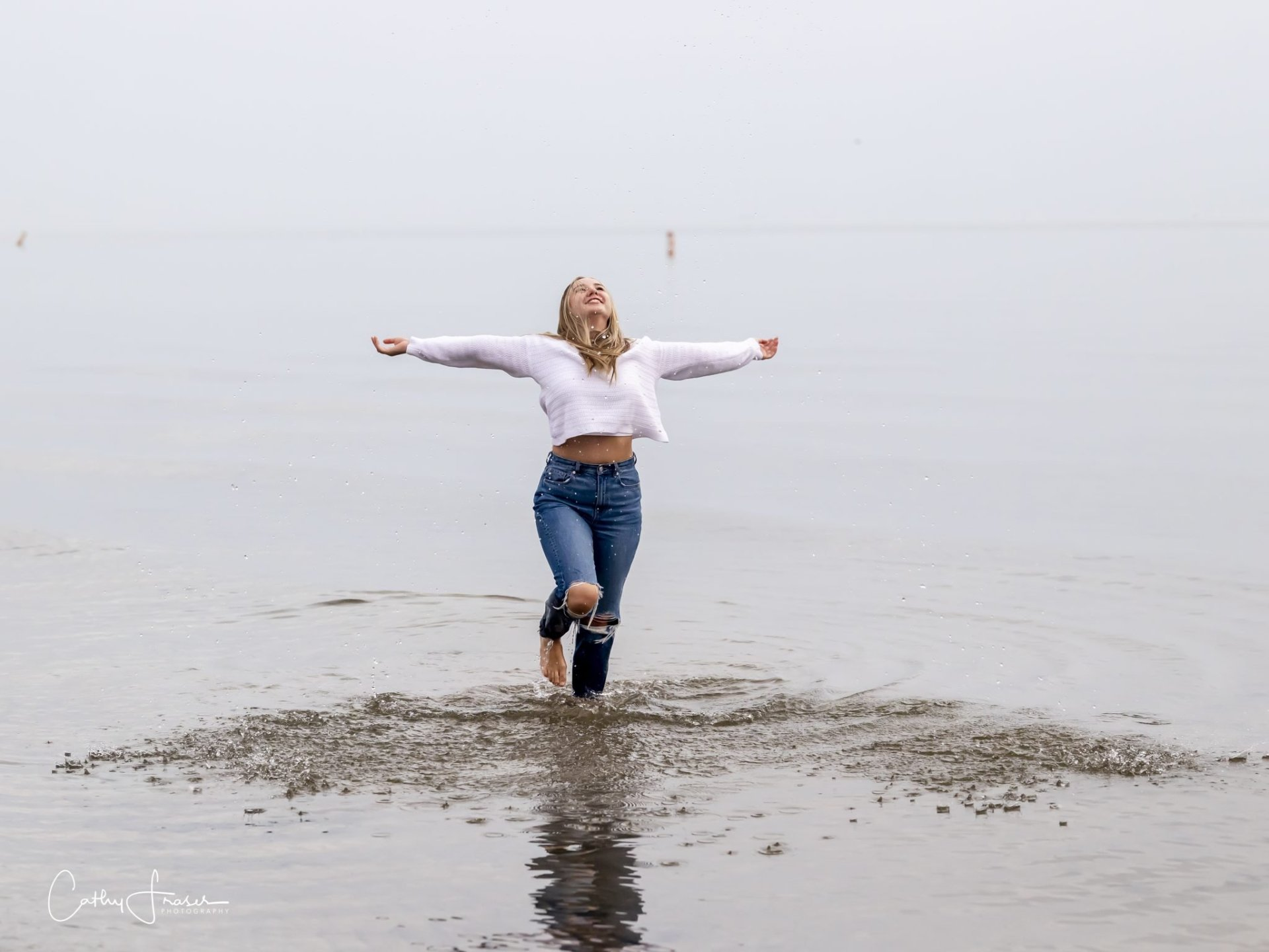joyful Girl in the surf, water , wearing blue jeans, white sweater, Ontario beach park, rochester, ny, high school senior professional pictures