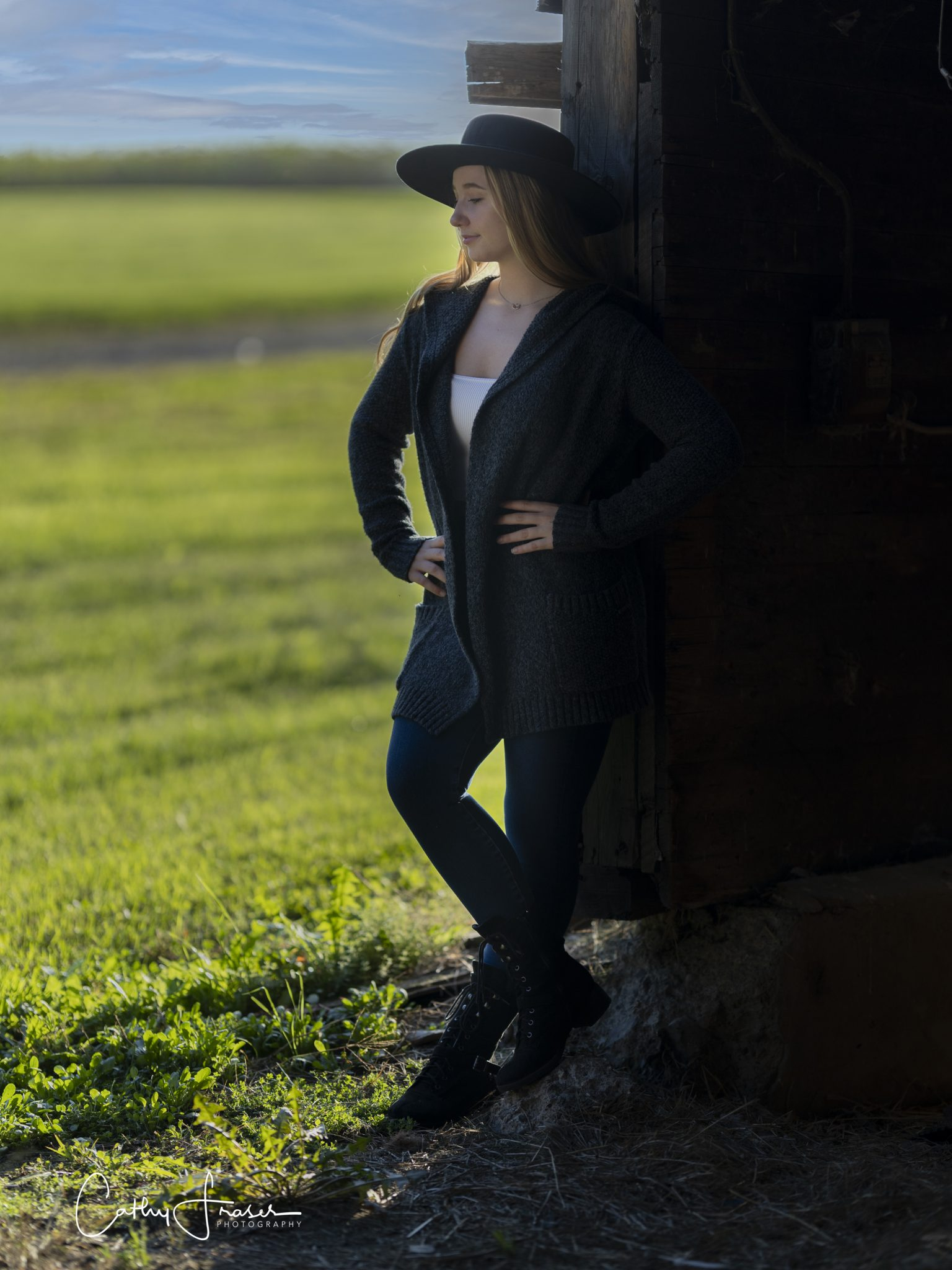 professional photo, natural light, girl wearing a black wide brimmed hat, sweater , Seneca, New York, leaning on a barn