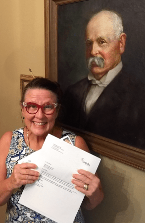 Aspiring author Cathy Krafve in front of a painting of her great grandfather, another author.