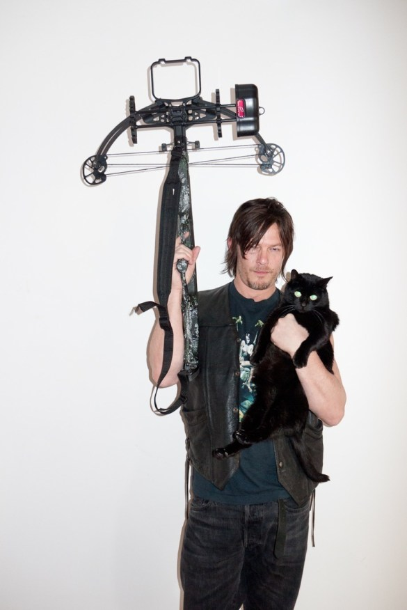 Norman Reedus posing with cat and crossbow
