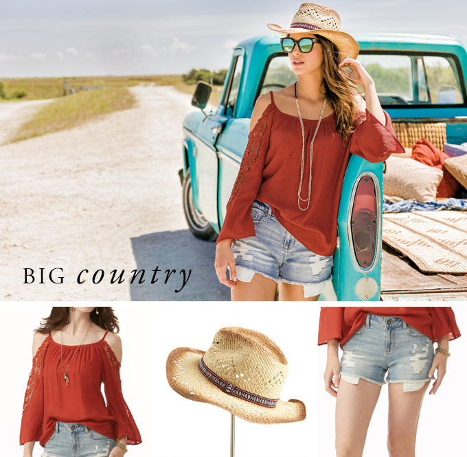 Big Country. A beautiful woman looks off into the distance wearing a lace detailed off the shoulder top, distressed jean shorts and a cowboy hat.