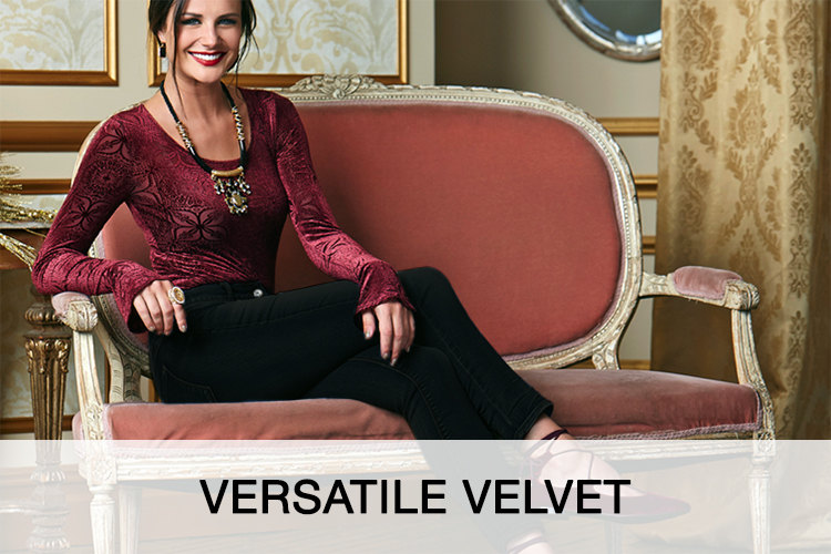 Versatile Velvet. A happy beautiful woman sitting on a couch wearing a velvet top and black pants.