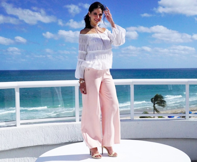 A beautiful woman outside at the beach wearing an off the shoulder top and wide leg pants.