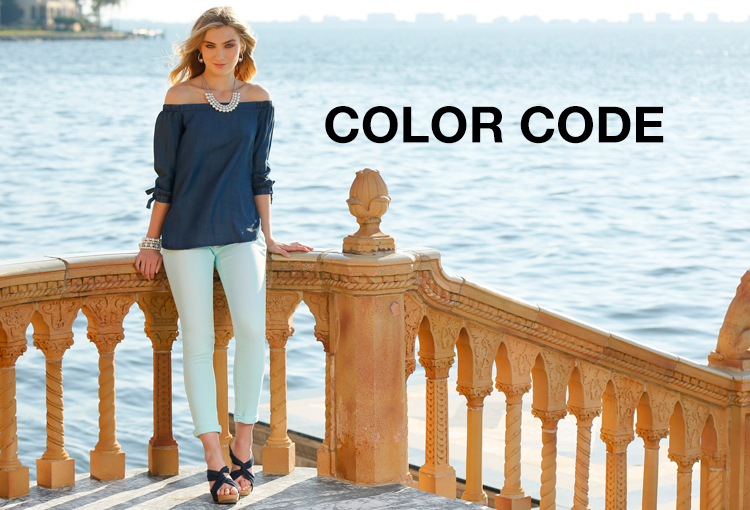 Color Code. A beautiful woman outside in front of the ocean wearing a light teal pair of ankle jeans.