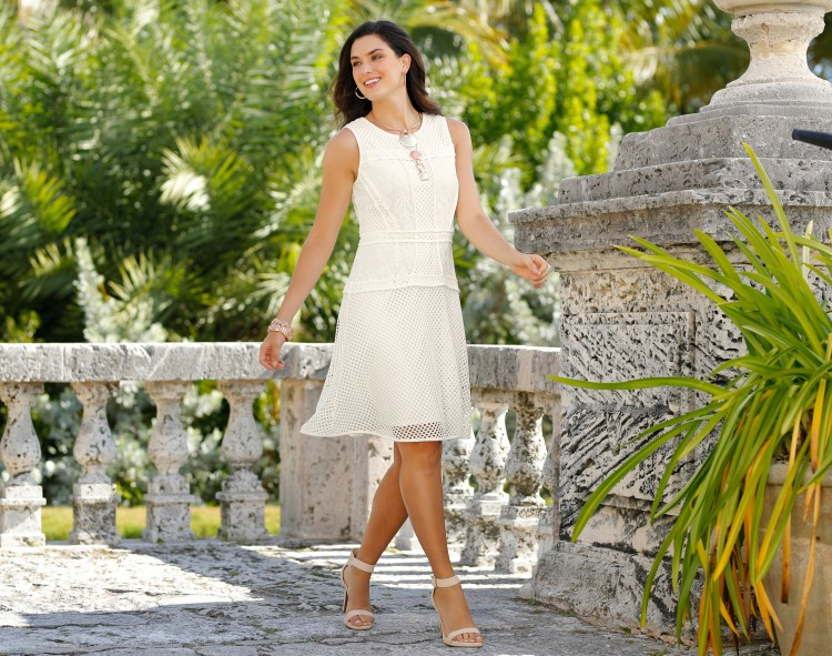 A beautiful woman in a flattering cream lace dress and nude heels.