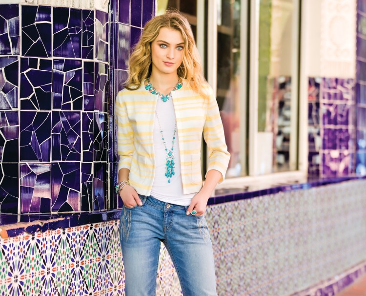 Model wearing a yellow striped jacket with turquoise jewelry and jeans