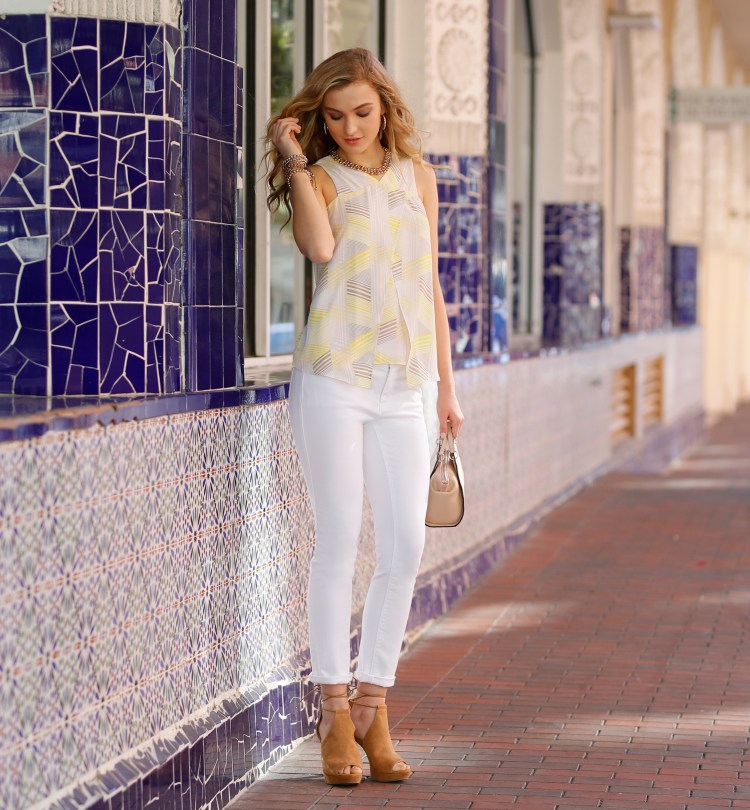 Model wearing a printed yellow sleeveless blouse and white denim