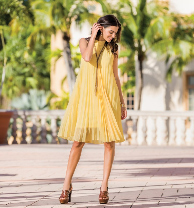Model wearing a bright yellow pleated dress with sandals and a tassel necklace