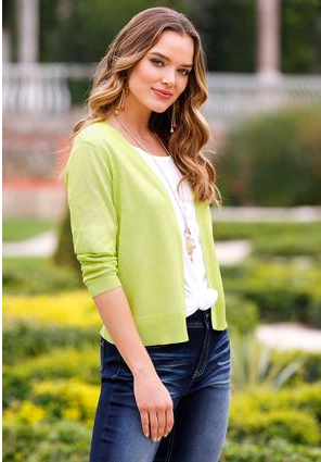 Model standing in front of greenery with a mesh knit cardigan on, whiskered jeans and a white tee.