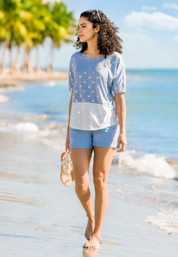 A modeal walking on the beach with shoes in her hand wearing a blue star tee and blue shorts.
