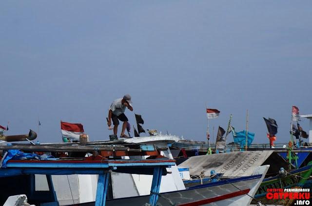 Waktu saya iseng berkeliling pulau, kebetulan saya melihat seorang yang sedang memperbaiki kapalnya.