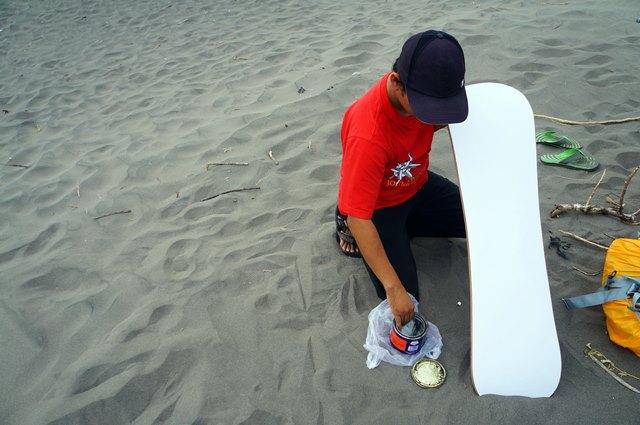 Mas Agus mengoleskan wax agar bagian bawah papan sandboarding menjadi licin.