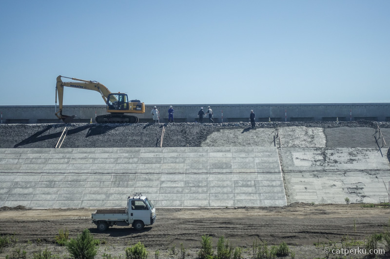 Mereka sedang membuat sea wall, dinding penahan tsunami. Ini saya foto dari dalam kereta.