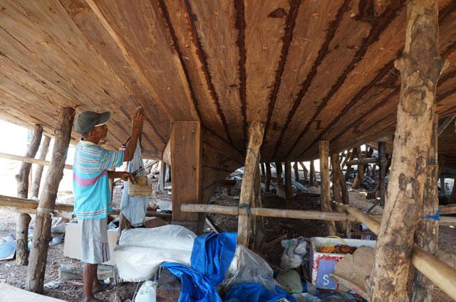 Seorang bapak yang sedang melakukan pembuatan Kapal Phinisi. Sepertinya sedang mengoleskan sesuatu ke bagian bawah kapal yang belum jadi.