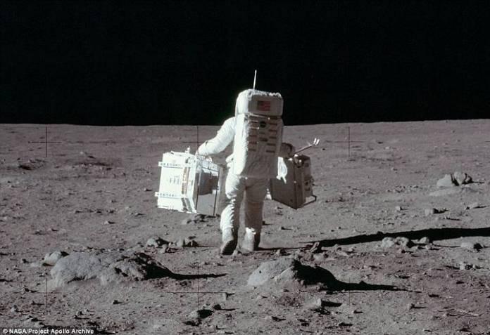 Aldrin carga equipos científicos sobre la superficie lunar para llevar a cabo experimentos sísmicos y recolectar muestras.