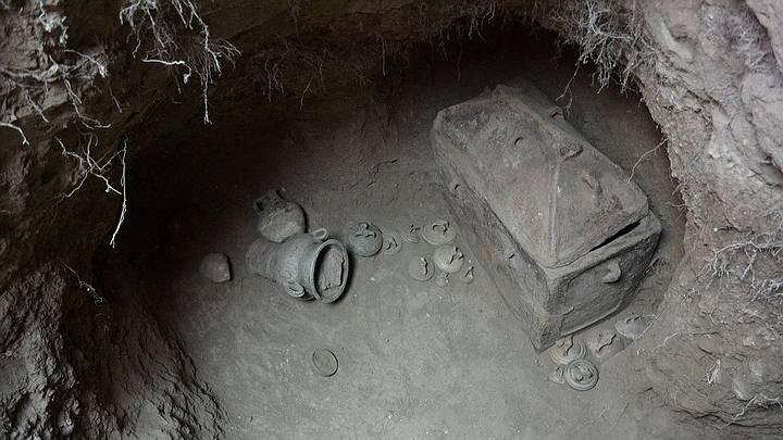 Sarcófago intacto con la tapa en su lugar y numerosas vasijas con forma de estribo.